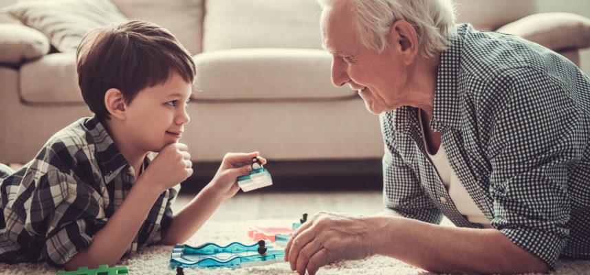 Abuelo jugando con nieto en el suelo